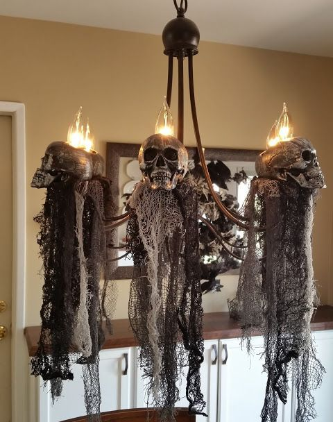 elegant and scary Halloween decor - a chandelier with skulls and black fabric down is a fantastic idea