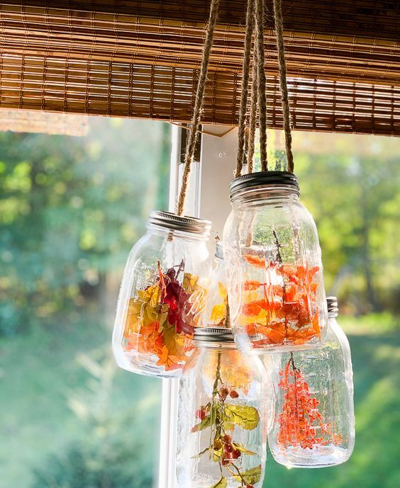 glasses with dried blooms, fall leaves and berries hanging over the space are a cool decoration in rustic style