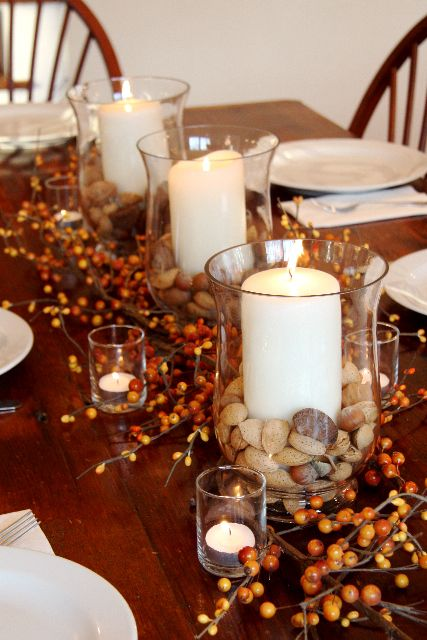 glasses with nuts and acorns and pillar candles for decorating the table for the fall