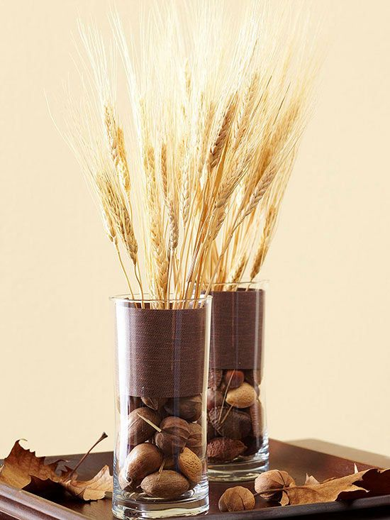 glasses with nuts and acorns, brown fabric and wheat compose a cool and natual fall centerpiece
