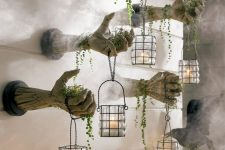 monster hands out of the wall with candle lanterns and greenery are scary and stylish Halloween decor to try
