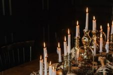 spooky and elegant Halloween table decor with hay, skulls, skeleton hands and lots of candles is fantastic