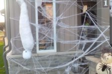 spooky outdoor Halloween decor with spiderwebs, spiders, a mummy and pumpkins all around