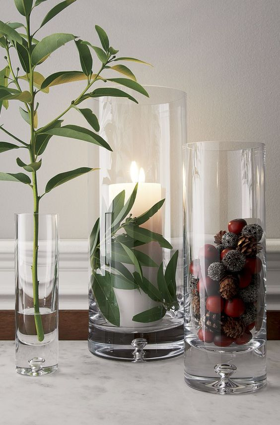 tall glasses with acorns and pinecones and a pillar candle and greenery for decorating for the fall in a modern way