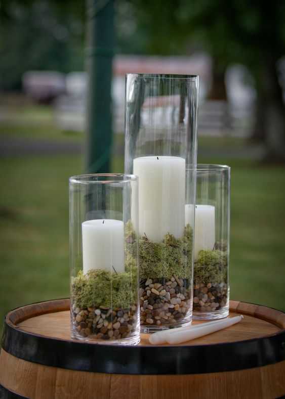 tall glasses with pebbles, moss and pillar candles are a cool centerpiece or fall decoration