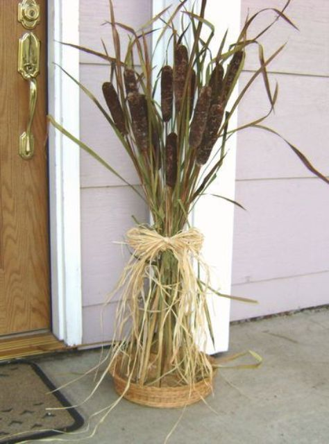 a cane and grass fall arrangement with hay and a woven tray is a cool idea for an outdoor space