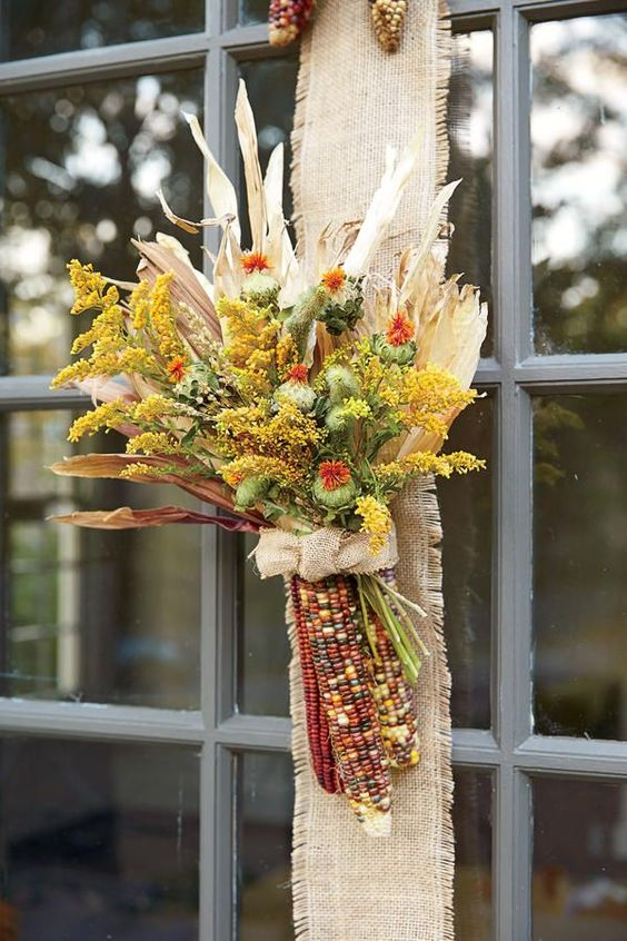 a dried fall arrangement with various blooms, corn husks and corn cobs and a burlap bow