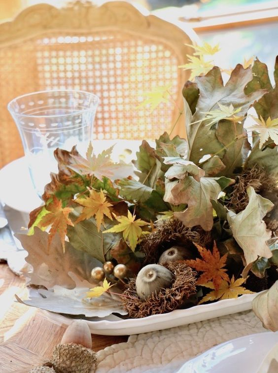 a dried fall centerpiece of a bowl with leaves, acorns, beads, figs and hay is a messy and cool one