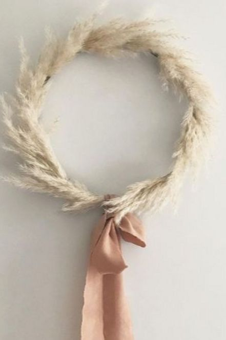 a dried wheat wreath with a brown bow is a cool fall decoration for any of your spaces