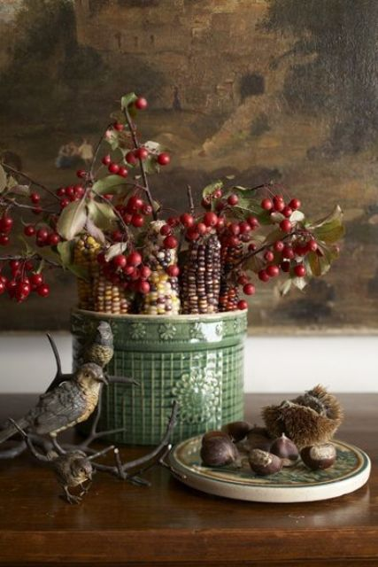 a fall arrangement of a green porcelain vase with berries and corn cobs is a lovely harvest centerpiece