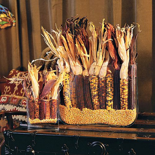 a fall centerpiece of glass jars with corn and corn cobs with husks is a bold and cool idea to rock