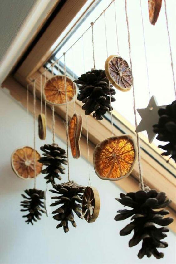 a fall window hanging of dried citrus slices and pinecones is a great decoration with a fall aroma