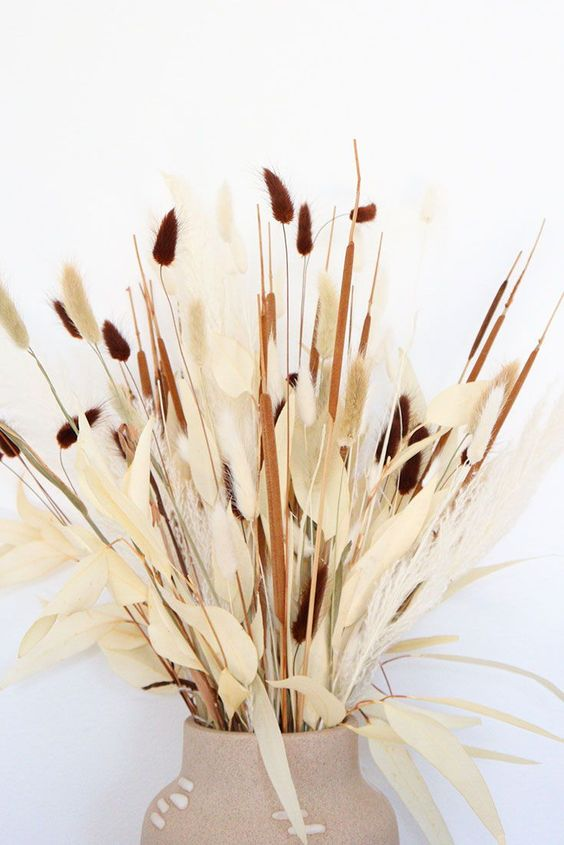 a gorgeous fall centerpiece or arrangement with bunny tails of various colors, dried husks and leaves