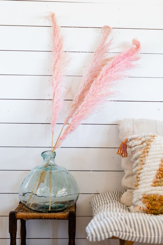 a large glass bottle with pink pampas grass is a playful and fun decoration you can easily make