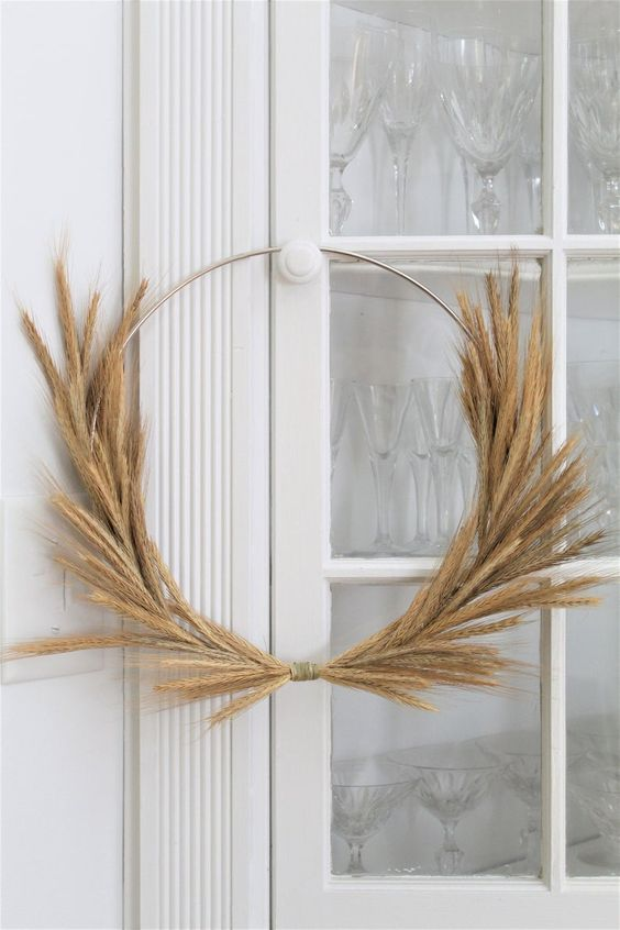a modern fall wreath of a metal form and wheat is a great idea for fall or Thanksgiving
