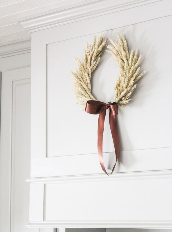 a stylish and laconic wheat fall wreath with a large brown silk bow for a contrasting accent