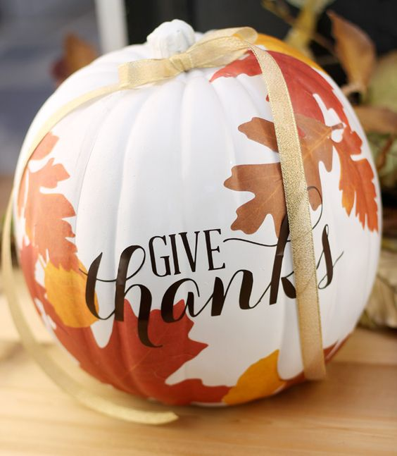 a super stylish white pumpkin with bright fall leaves attached and a gold glitter ribbon is ultimate