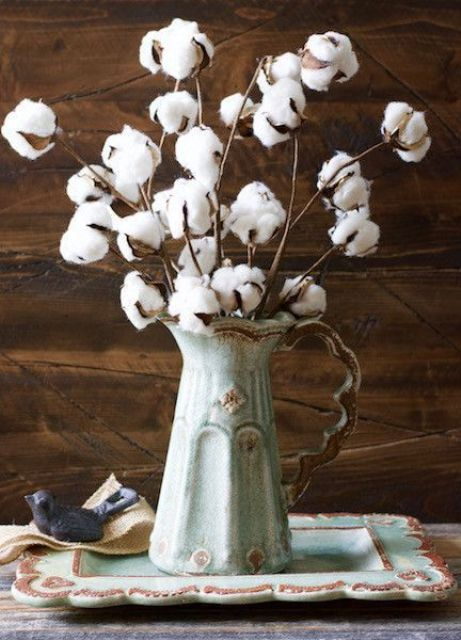 a vintage jug with cotton branches is a cool and veyr easy fall centerpiece with a refined feel