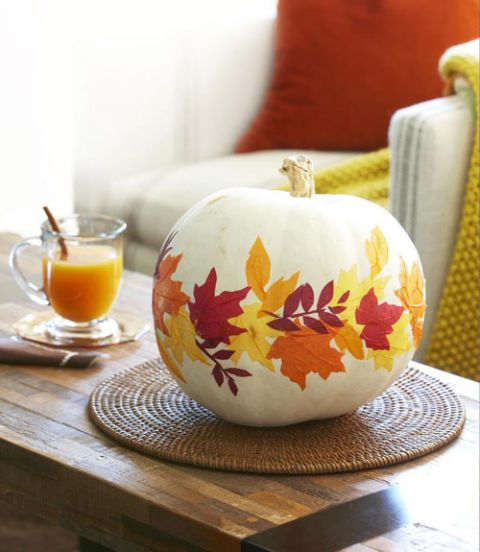 a white pumpkin decoupaged with bright fall leaves is a very bold and natural craft to make