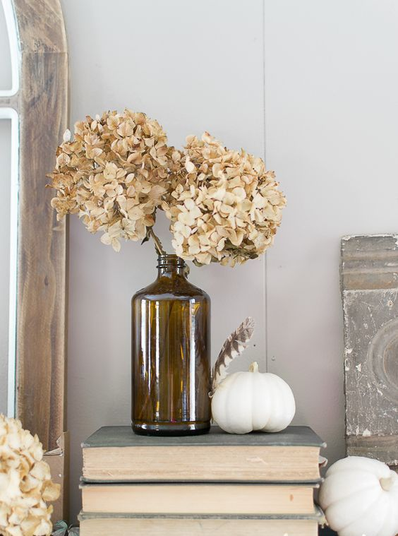 an apothecary bottle with dried hydrangeas and a white pumpkin is a simple and cute fall arrangement