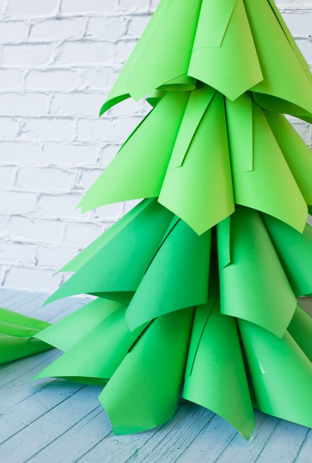 Paper cone Christmas trees is an expensive holiday craft project. All you need is a few packs of paper and a bow.