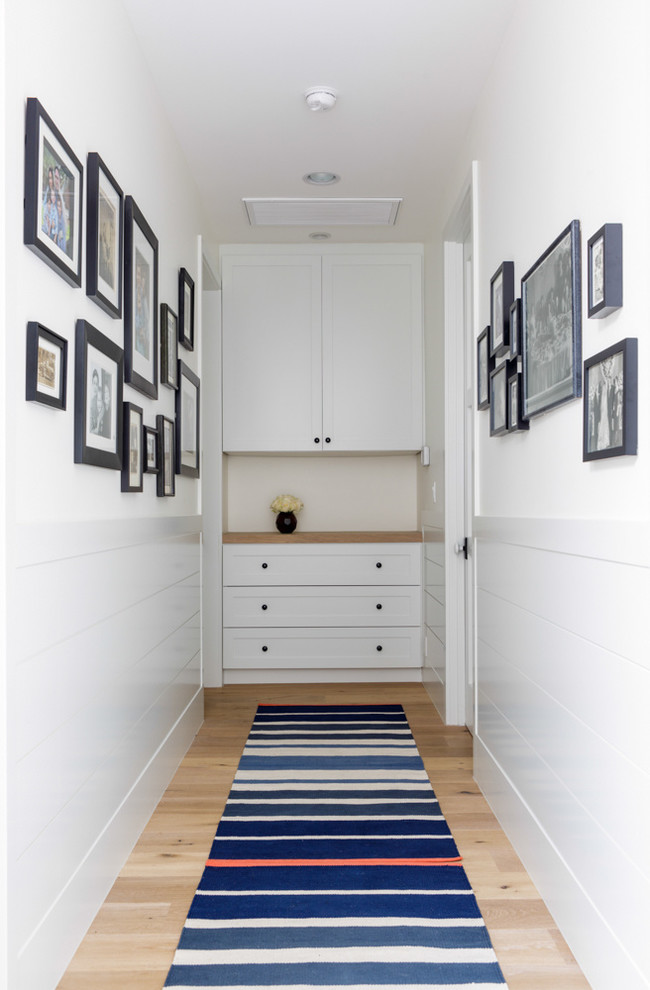 simple hallway design with a photo gallery wall and a built-in cabinet that provides linen storage