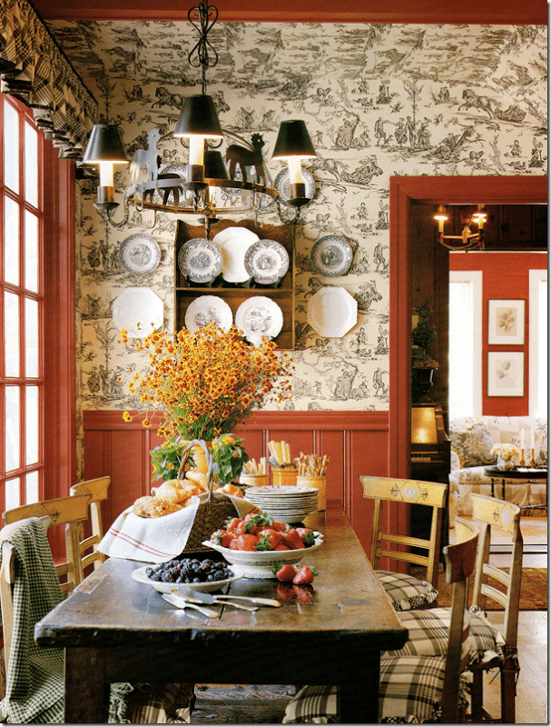 Pretty country dining room with wallpaper & colonial red trim & antique pine table