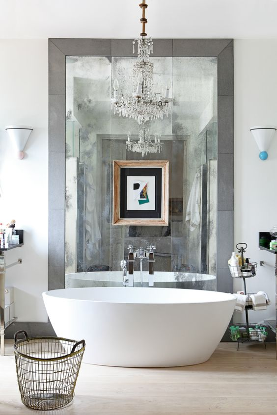 a contemporary bathroom in neutral shades, an oval tub, a large mirror in tiles, a crystal chandelier