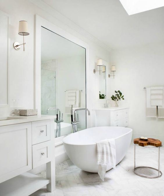 a contemporary bathroom in neutrals, with an oval tub, a large mirror and a double vanity plus lamps