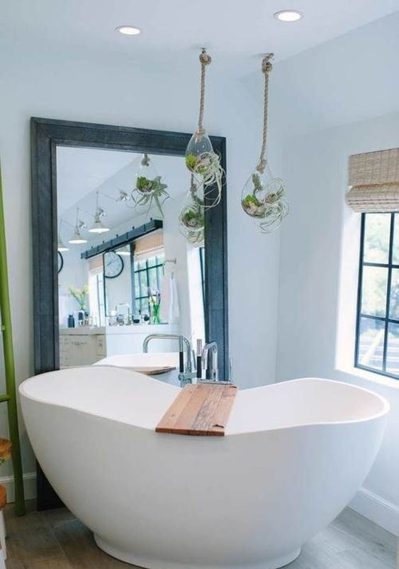 a contemporary bathroom with a free-standing bathtub, a large floor mirror leant to the wall, air plants in glass bubbles