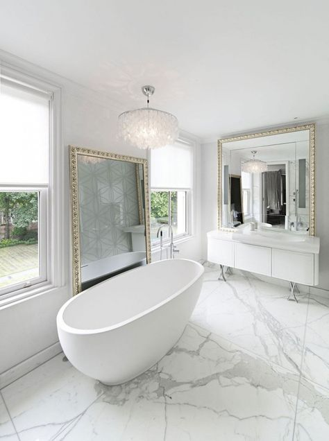 a contemporary luxurious space done in white marble, with two large mirrors in gorgeous frames and a crystal chandelier
