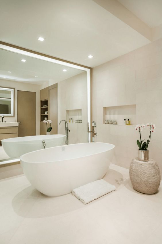 a minimalist bathroom in neutrals, an oval tub, a large lit up mirror wall, a potted orchid and a built-in shelf