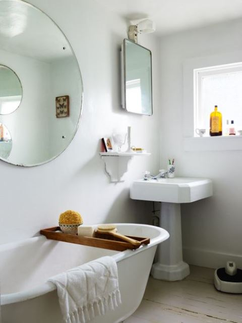 a natural bathroom with a small sink, a free-standinf tub, a round mirror and some cool and simple accessories