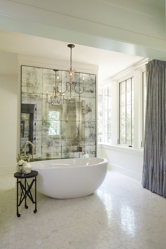 a refined glam bathroom in neutrals with an oval tub, a chic chandelier and a dark mirror wall