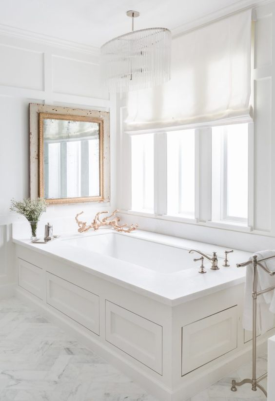 a serene bathroom done in white marble, with a crystal chandelier, a vintage mirror over the tub