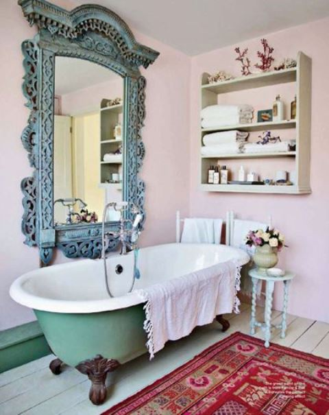 a shabby chic bathroom with pink walls, a green clawfoot tub, a patina ornate frame mirror and a shelf