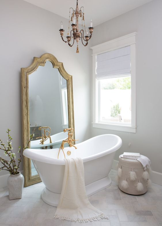a vintage bathroom in neutrals, with a statement mirror, a vintage chandelier, a retro tub and gold fixtures