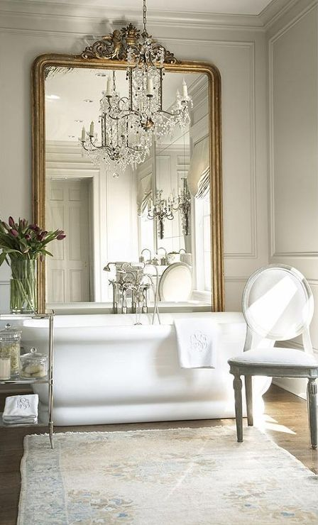 a vintage bathroom with a large tub, an ornate vintage mirror, a crystal chandelier and some refined furniture