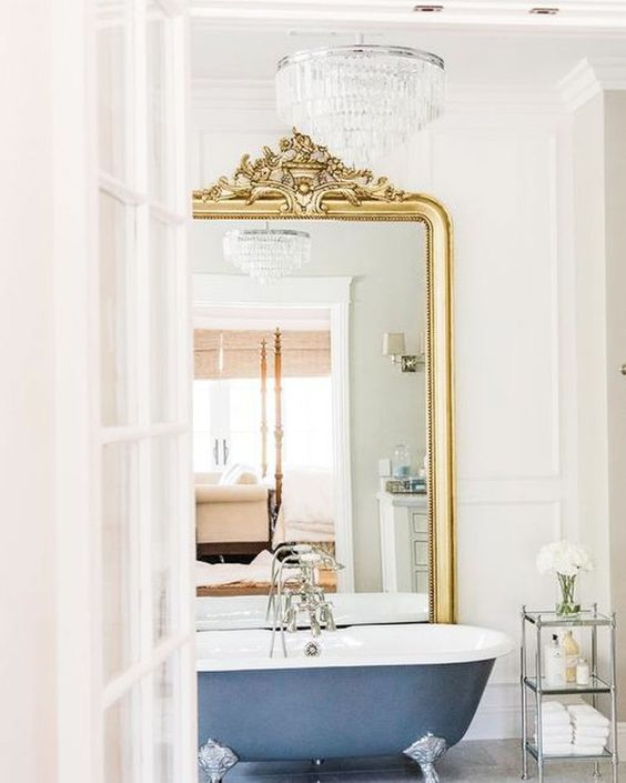 a vintage bathroom with molding, a navy bathtub, a crystal chandelier and a mirror in a gold ornate frame