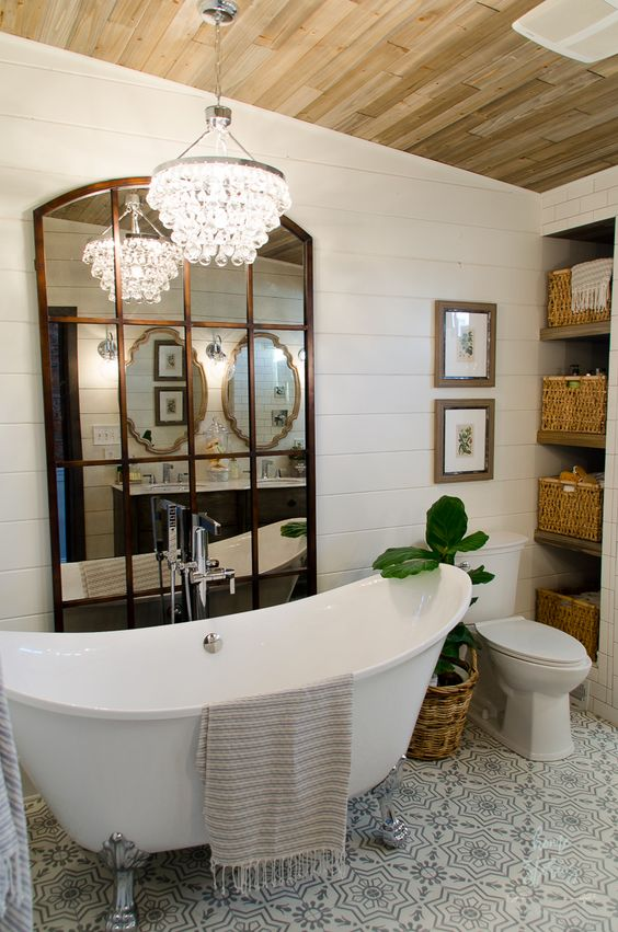 a vintage rustic bathroom with a clawfoot tub, baskets for storage, a crystal chandelier and a framed mirror on the wall