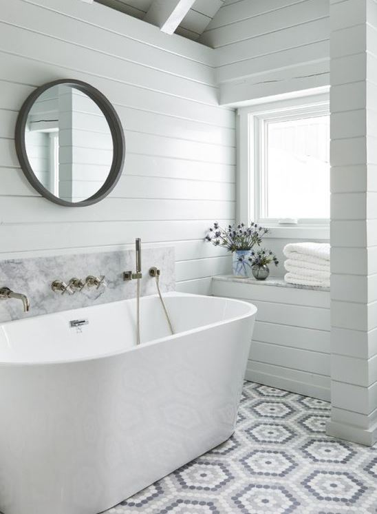 a white contemporary bathroom clad with white wooden planks, mosaic tiles, an oval tub and a round mirror