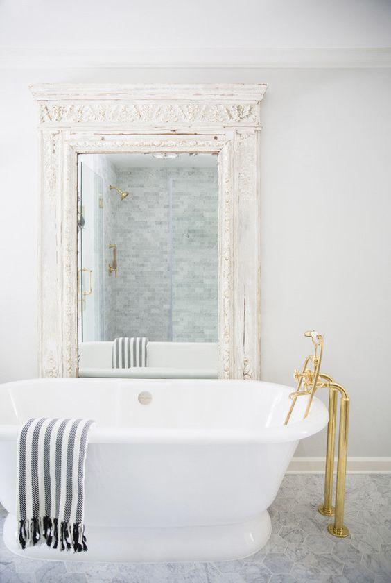 an eclectic bathing space with a white tub, gold fixtures, a vintage mirror in an ornate whitewashed frame