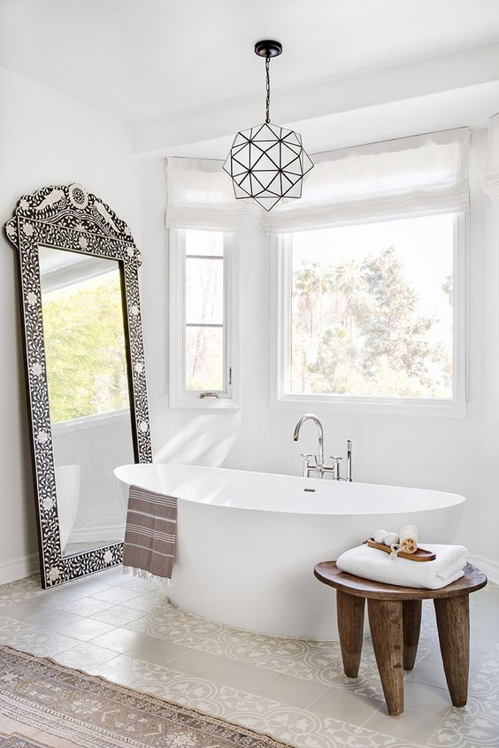 an eclectic bathroom in neutrals, an oval tub, a wooden stool, a 3D chandelier and an ornate frame mirror