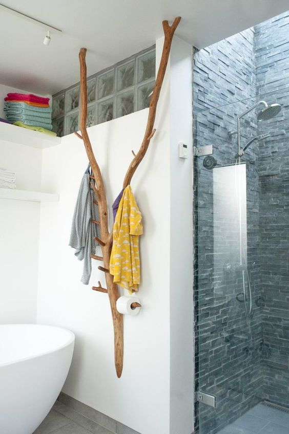 a creative bathroom hanger and holder made of some tree branches and hooks attached to them