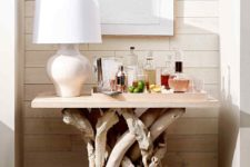 a home bar made of a piece of plywood and bleached driftwood branches for the legs is a stylish idea
