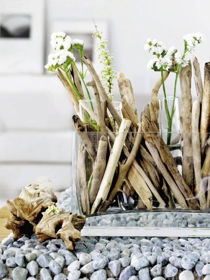 a spring centerpiece of driftwood, test tubes with white blooms looks super natural and very chic