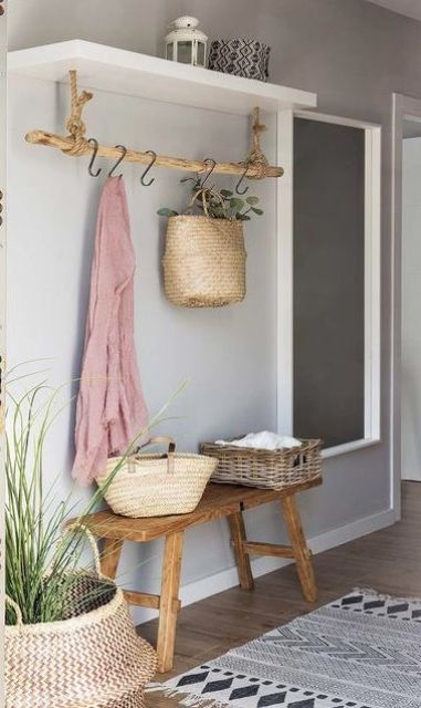 an entryway holder made of a branch on rope with hooks is a stylish rustic idea to go for
