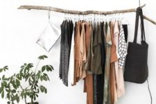 an open closet with a branch as a holder for clothes – bring a touch of nature to your space