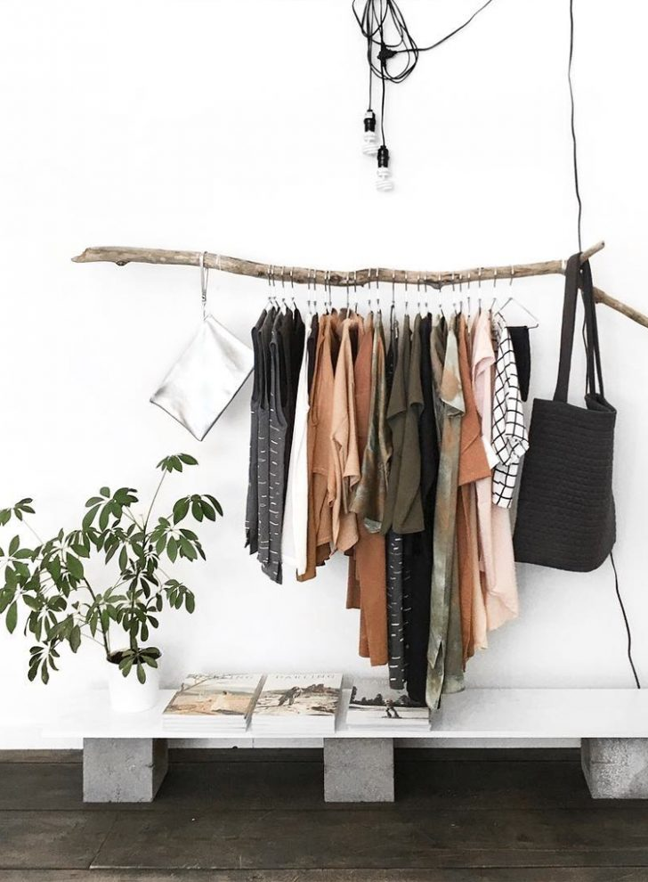 an open closet with a branch as a holder for clothes - bring a touch of nature to your space