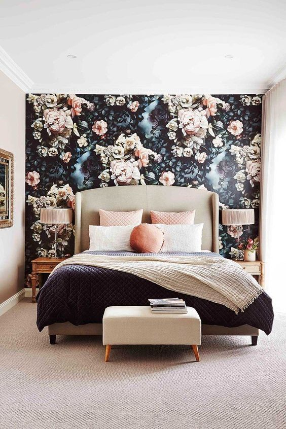 a chic bedroom with a dark floral accent wall and a blanket and throws to match its colors